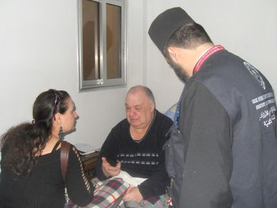 Yvette with a priest of the Greek Orthodox church visiting a victim of a Jabat Al Nusra attack.