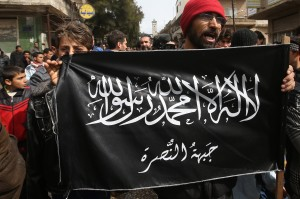 FILE- In this Friday, March 1, 2013 file photo, anti-Syrian President Bashar Assad protesters hold the Jabhat al-Nusra flag, as they shout slogans during a demonstration, in Kafranbel, Idlib province, northern Syria. Under the relative calm of Syria's shaky cease-fire, peaceful protests in opposition-held parts of the country have re-emerged, but in addition to Syrian President Bashar Assad's government, protesters have found another authority to topple: Al-Qaeda's affiliate in Syria, the oppressive Nusra Front group. (AP Photo/Hussein Malla, File)