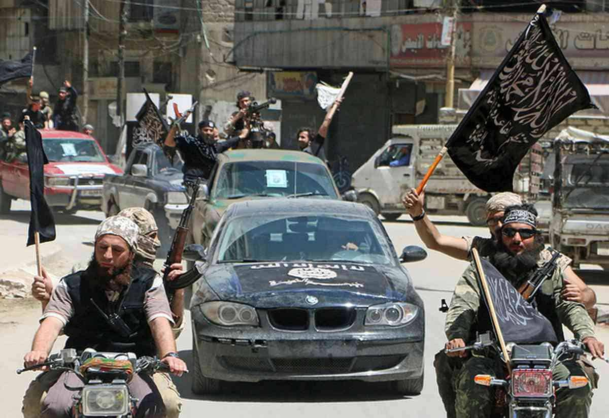 Fighters from Al-Qaeda's Syrian affiliate Al-Nusra Front drive in the northern Syrian city of Aleppo flying Islamist flags as they head to a frontline, on May 26, 2015. Once Syria's economic powerhouse, Aleppo has been divided between government control in the city's west and rebel control in the east since shortly after fighting there began in mid-2012. AFP PHOTO / AMC / FADI AL-HALABI / AFP PHOTO / AMC / Fadi al-Halabi